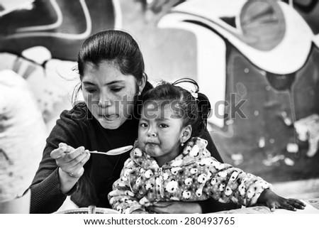 OTAVALO, ECUADOR - JAN 3, 2015: Unidentified Ecuadorian mother and her daughter at the Otavalo Market. 71,9% of Ecuadorian people belong to the Mestizo ethnic group #280493765