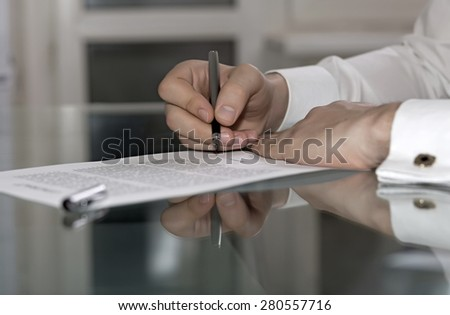 Man signs formal paper. Businessman hands working on paper document on glass office table making strong reflection with fountain pen stylish shirt with golden cuff link soft smothered background