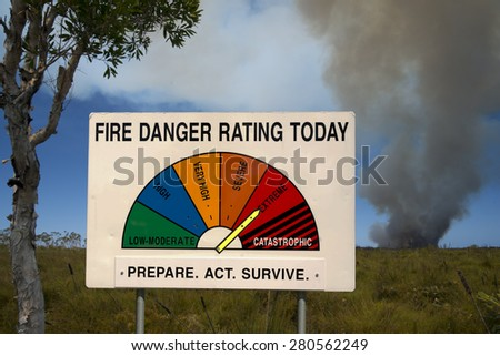Fire Danger Rating Display Board set to extreme while bushfire smoking in background. Image taken in Queensland, Australia.