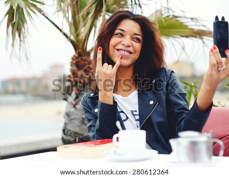 Young hipster girl taking self portrait with phone camera doing sign of the horns or rock hand gesture, afro american woman having fun while photographing herself with smart phone in coffee shop