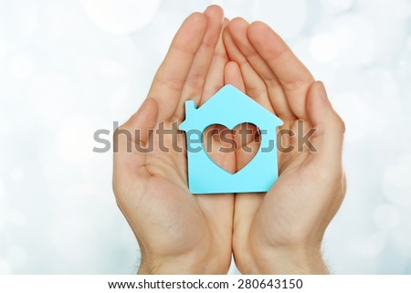 Female hands holding house on light blurred background #280643150