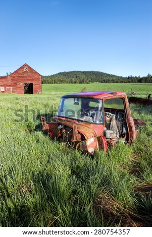 Old truck in grass near a red barn south of Tensed, Idaho. #280754357