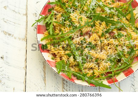 Italian pasta fusilli with fresh garlic and rocket leaves, spanish chorizo, parsley, parmesan cheese on gingham plate, white wood background #280766396