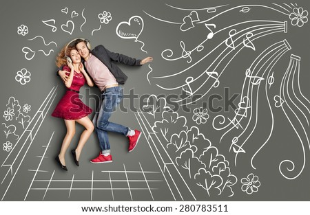Happy valentines love story concept of a romantic couple walking in the park, sharing headphones and listening to the music against chalk drawings background.