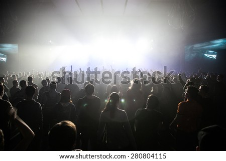 MOSCOW-2 FEBRUARY,2015:Huge concert crowd on music festival in night club.Super bright stage lighting on concert.Music fans partying in nightclub.Rave party people.Concert crowd on dance floor in club #280804115