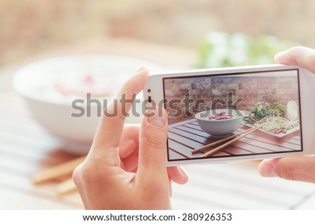 Closeup view of lifeview process on a smartphone for taking a picture of Pho Bo in street cafe in Vietnam. The Pho Bo is a traditional Vietnamese beef noodle soup. Popular healthy street food.