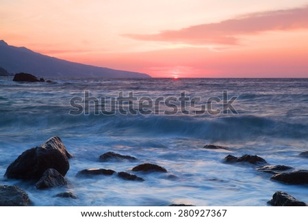 Waves break about stones at sunrise over the sea #280927367