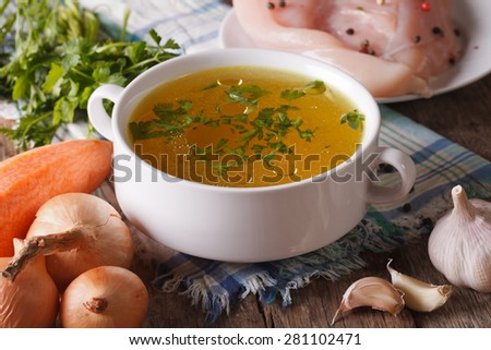 Chicken broth in a bowl and ingredients on the table close-up. Horizontal