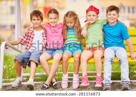 Group of friendly kids sitting on bench outside #281156873