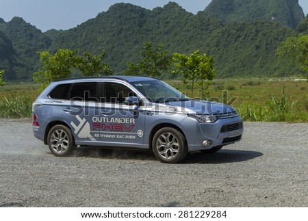 Ha Noi, Viet Nam - May 18, 2015: The Mitsubishi Outlander PHEV plug-in Hybrid CUV running on the bad road in Vietnam #281229284