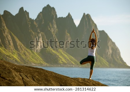 Young woman is practicing yoga between mountains in Norway Royalty-Free Stock Photo #281314622
