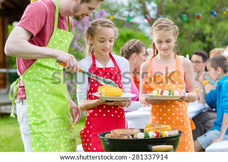 Family having barbecue at garden party, dad is putting corn and grilled vegetables on plates of daughters #281337914