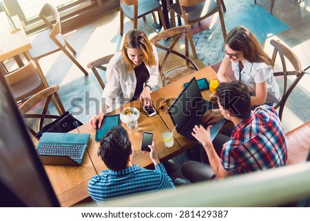Group of young people sitting at a cafe, talking and enjoying, top view Royalty-Free Stock Photo #281429387