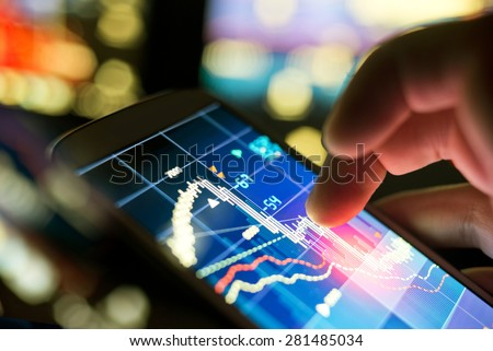 A businessman using a mobile phone to check stock market data. Royalty-Free Stock Photo #281485034