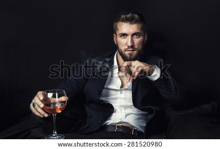 Attractive man with a cigar, and a glass of wine in his hands #281520980