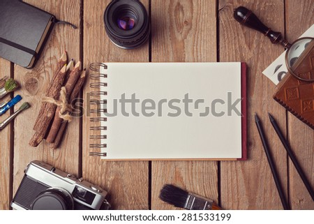Notebook mock up for artwork or logo design presentation with film camera and lens. View from above