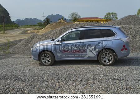 Ha Noi, Viet Nam - May 18, 2015: The Mitsubishi Outlander PHEV plug-in Hybrid CUV car running on the rocky gravel stones road in Vietnam #281551691