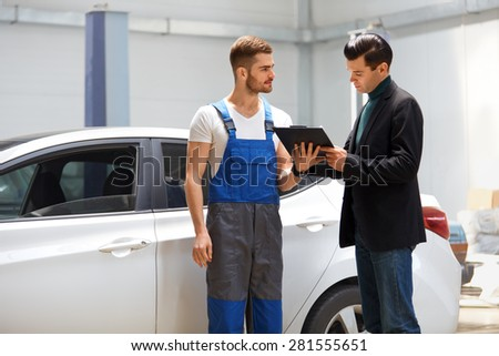 Customer Looking at the Service Report in a Repair Shop #281555651