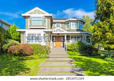 Custom built luxury house with nicely trimmed and designed front yard, lawn in a residential neighborhood in Canada. #281691164