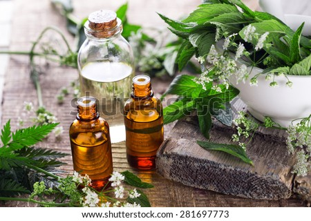 Bottles with organic essential aroma oil with mint  on aged wooden background. Selective focus.  #281697773