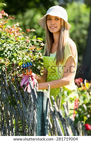 young woman florists in apron working in the garden #281719004