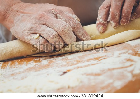 Close up photo of baker kneading dough with a rolling pin. Retro styled imagery. Grain added #281809454