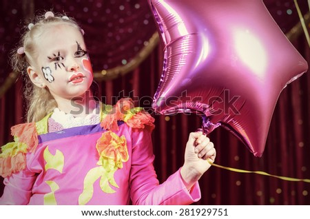 Head and Shoulders Portrait of Young Blond Girl Wearing Clown Make Up and Costume Holding Star Shaped Balloon on Stage in front of Red Curtain #281929751
