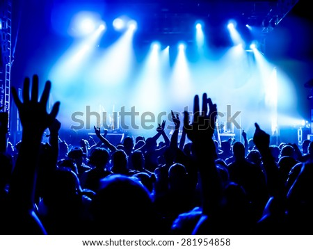 silhouettes of concert crowd in front of bright stage lights #281954858