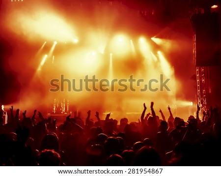 silhouettes of concert crowd in front of bright stage lights #281954867
