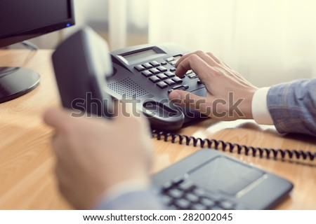 businessman dialing voip phone in the office, keyboard and monitor detail in the background with vintage color tone effect #282002045