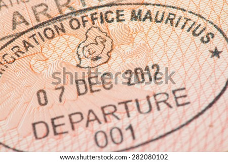 Passport page with Mauritius immigration control departure stamp with traditional Dodo bird depicted on it.  #282080102