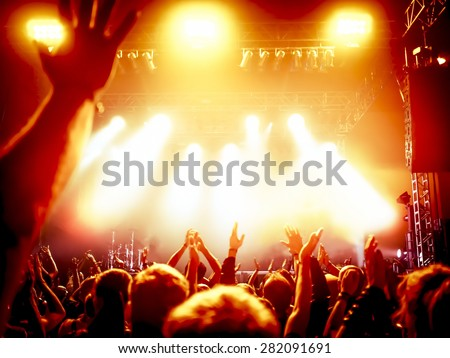 silhouettes of concert crowd in front of bright stage lights #282091691