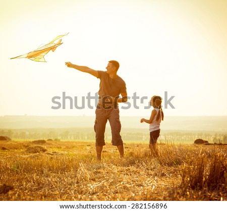Dad with his little daughter let a kite in a field #282156896