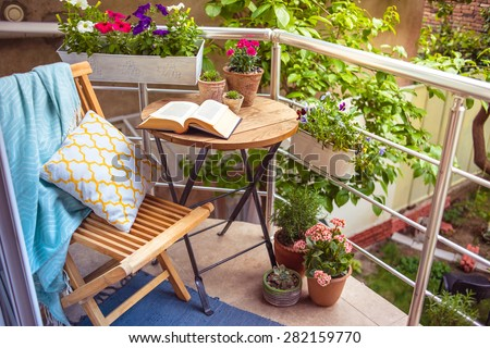 Beautiful terrace or balcony with small table, chair and flowers Royalty-Free Stock Photo #282159770