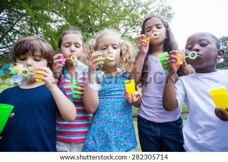 Little friends blowing bubbles in park on a sunny day #282305714