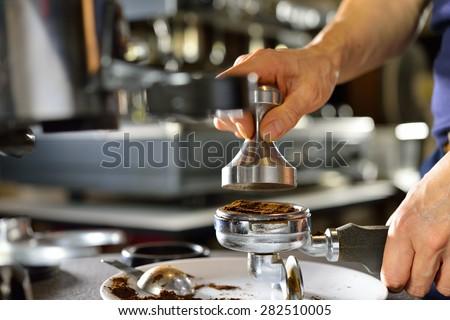 Barista using a tamper to press ground coffee into a portafilter #282510005