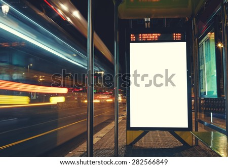 Illuminated blank billboard with copy space for your text message or content, advertising mock up banner of bus station, public information board with blurred vehicles in high speed in night city  Royalty-Free Stock Photo #282566849