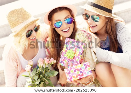 A picture of a group of friends making a surprise birthday present