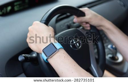 SEATTLE, USA - May 30, 2015: Man Wearing Apple Watch While Driving Toyota Prius #282735101
