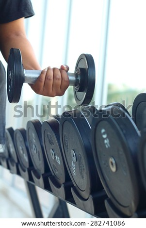 strong women hand takes a heavy dumbbell in gym #282741086