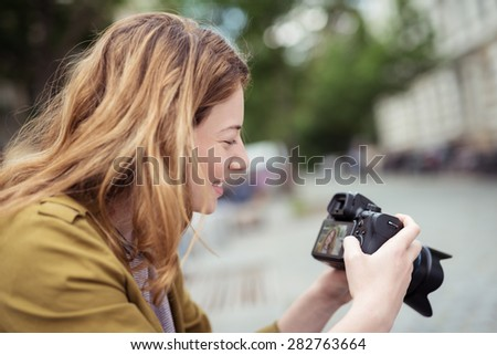 Close up Smiling Teen Blond Girl Looking at her Captured Outdoor Photos on her DSLR Photo Camera.