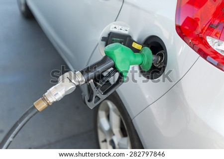 Petrol pump nozzle placed in silver car's petrol tank ready to fill up. Shallow focus on nozzle. Image shows part of car's tail light. Petrol nozzle head is green plastic. #282797846