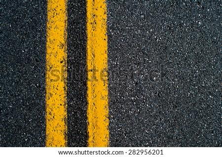 Double yellow line on black asphalt road.  #282956201