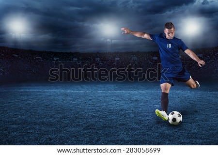 Professional soccer or football player during game in full floodlit stadium at night #283058699