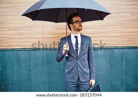 Young entrepreneur with briefcase standing outside under umbrella #283137044