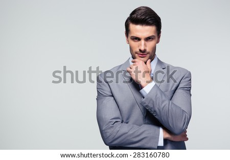 Portrait of a pensive businessman touching his chin over gray background Royalty-Free Stock Photo #283160780