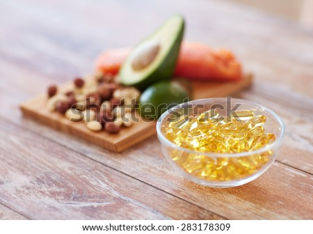 healthy eating, diet and omega 3 nutritional supplements concept - close up of cold liver oil capsules in glass bowl and food on table #283178309