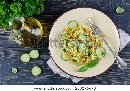 Cabbage salad with cucumber and carrots. Salad and vegetables on wooden table #283275698