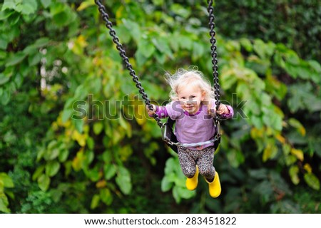 Happy little toddler girl wearing gumboots and warm vest having fun on a swing in the park on a chilly autumn or summer day #283451822