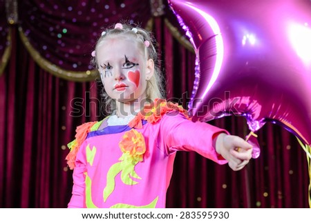 Head and Shoulders Portrait of Young Blond Girl Wearing Clown Make Up and Costume Holding Star Shaped Balloon on Stage in front of Red Curtain #283595930